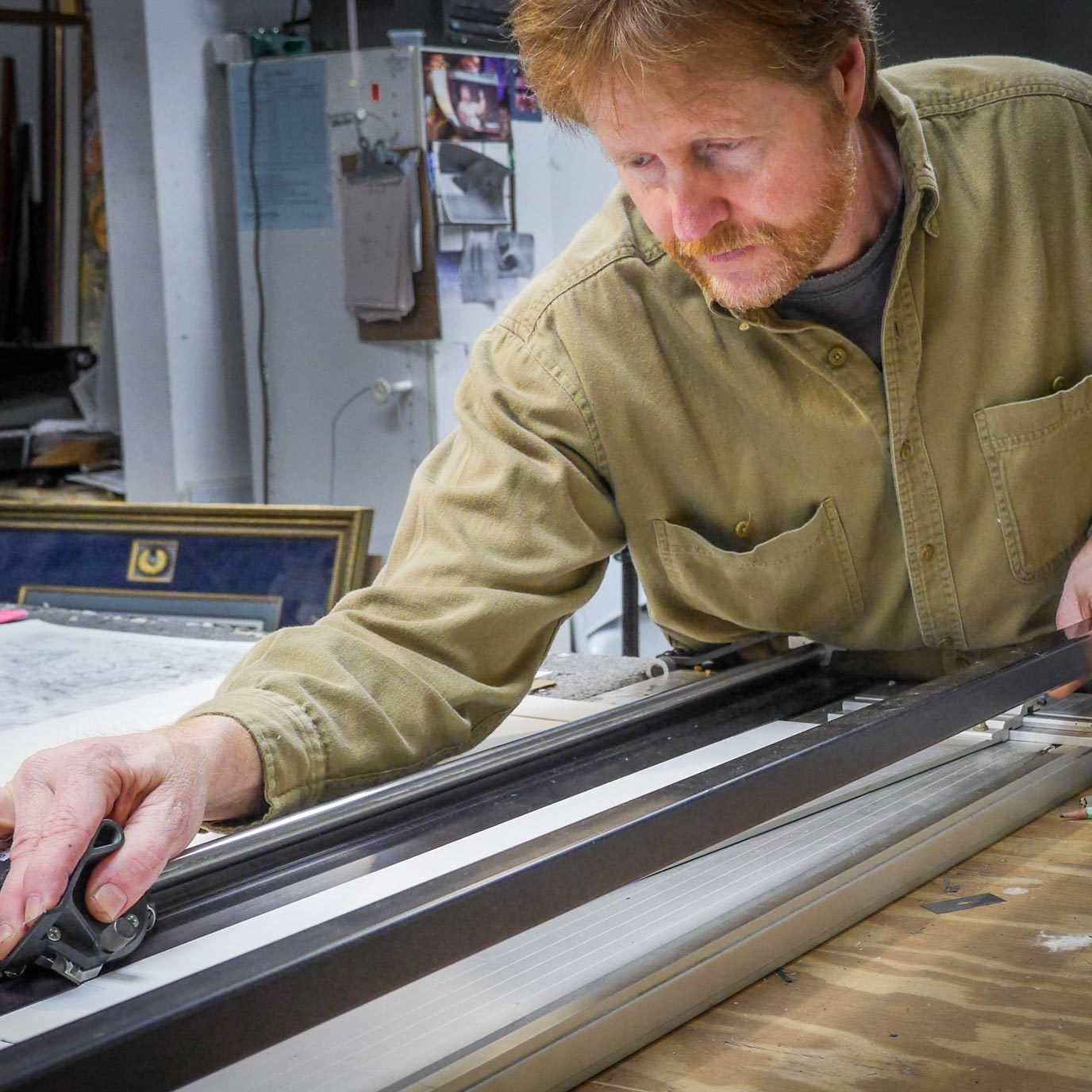 Cutting a mat for custom picture framing in Fayetteville, NC.